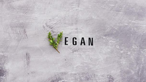 hand placing fork and knife next to Vegan text with V made from small branches with leaves, concept of healthy plant-based diet and animal rights