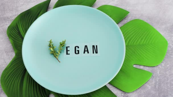 hand placing fork and knife next to Vegan text with V made from small branches with leaves on plate with tropical leaf underneath, concept of healthy plant-based diet and animal rights