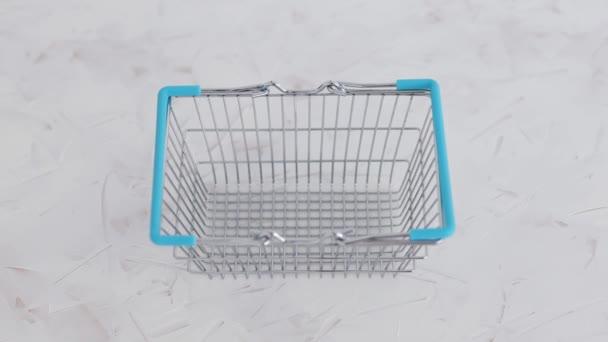 ruční umístění dezinfekční láhev uvnitř nákupního košíku symbol vysoce vyhledávané produkty v době vlastní izolace a karantény