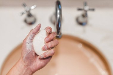flattening the curve through hygiene against pandemic outbreaks like covid-19, woman washing her hands in the bathroom holidng soap bar shot at shallow depth of field