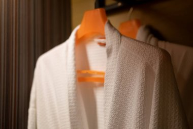 Soft comfortable bathrobes hanging on rack in closet in hotel