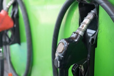 Close up of black fuel nozzle in oil dispenser at pump station