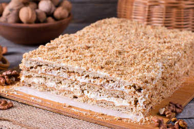 Delicious honey cake with sweet sour cream, and nuts on a rustic background