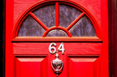 House number 64 in bright red with a semicircle of glass as a window and a door knocker