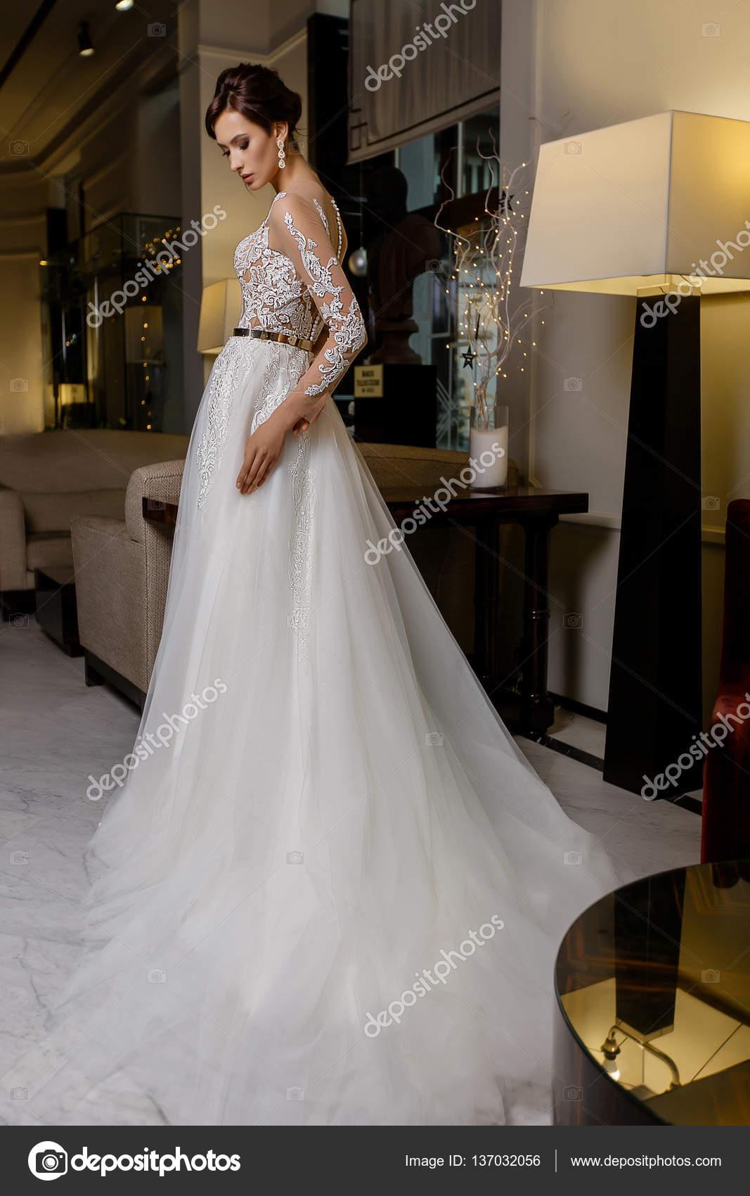 Schöne junge Brünette Modell weibliche Posen in lange Brautkleid mit ...