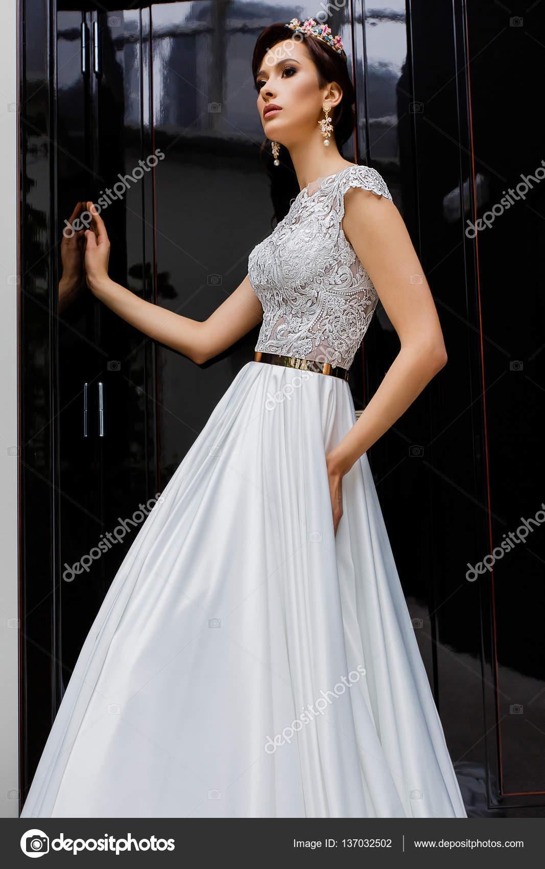 Junge schöne Modell weibliche Posen in langen Brautkleid weiß und ...
