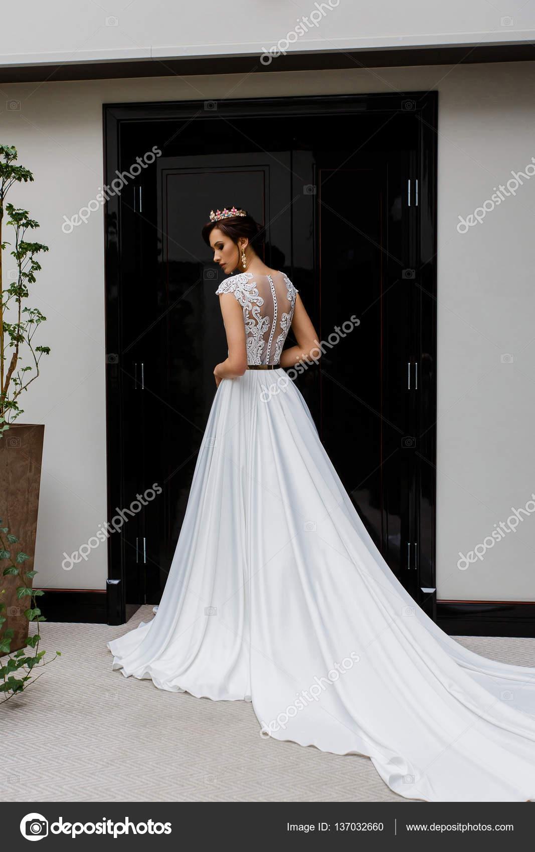 Junge attraktive Modell weibliche Posen in langen weißen Brautkleid ...