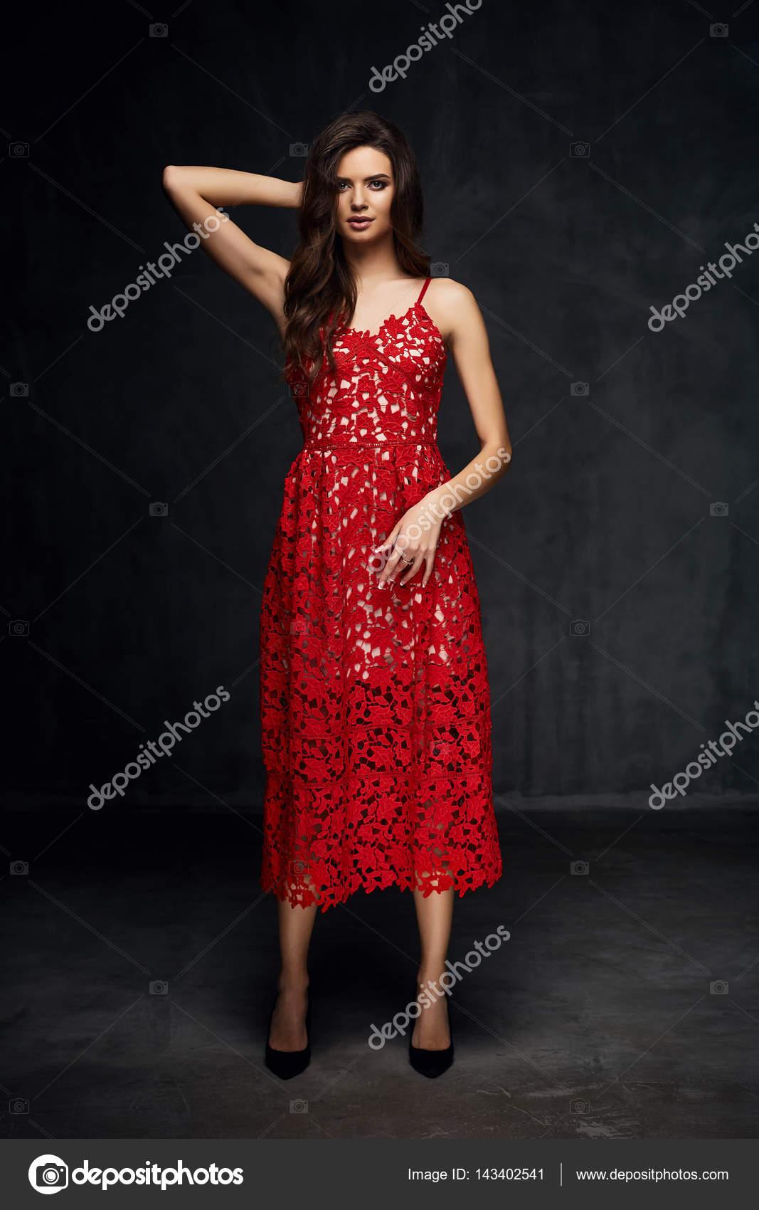 Hezká mladá sexy modelu žena s tmavými vlasy v úžasné červené krajkové šaty  a černé boty pózuje v tmavých studio– stock obrázky abcc9f5780