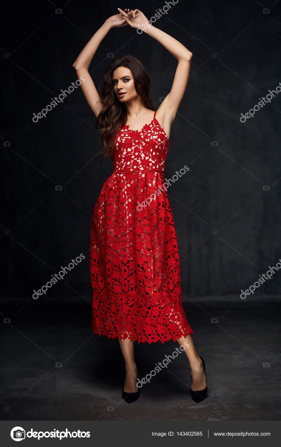 a077d37539be Όμορφη νεαρή σέξι μοντέλο θηλυκό με σκούρα μαλλιά στο καταπληκτικό καιρό κόκκινη  δαντέλα φόρεμα και μαύρα