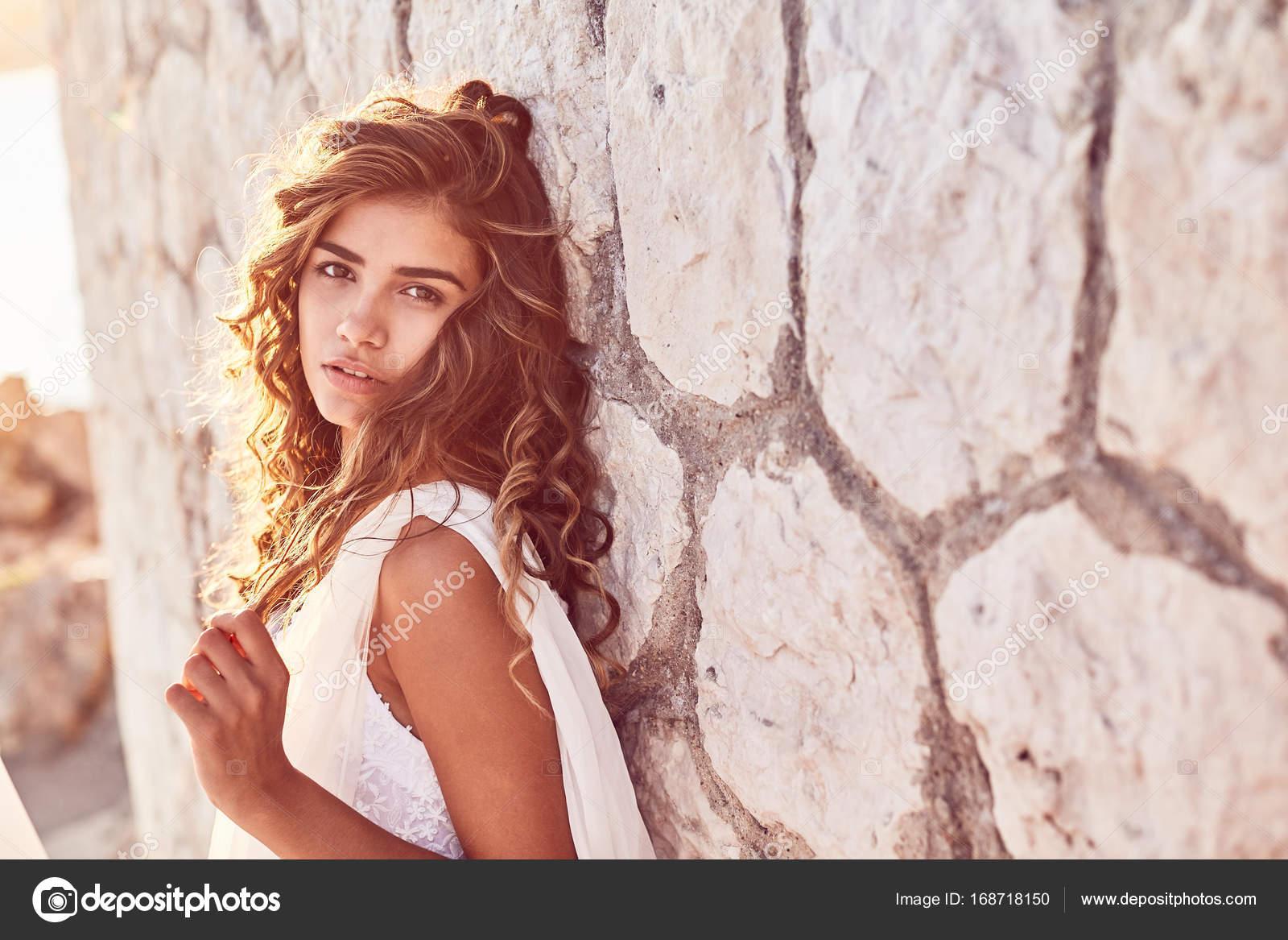 Úžasný portrét krásné sexy mladá žena model s dlouhé kudrnaté tmavé vlasy  nosí dlouhé bílé šaty eaaf84b2ed1