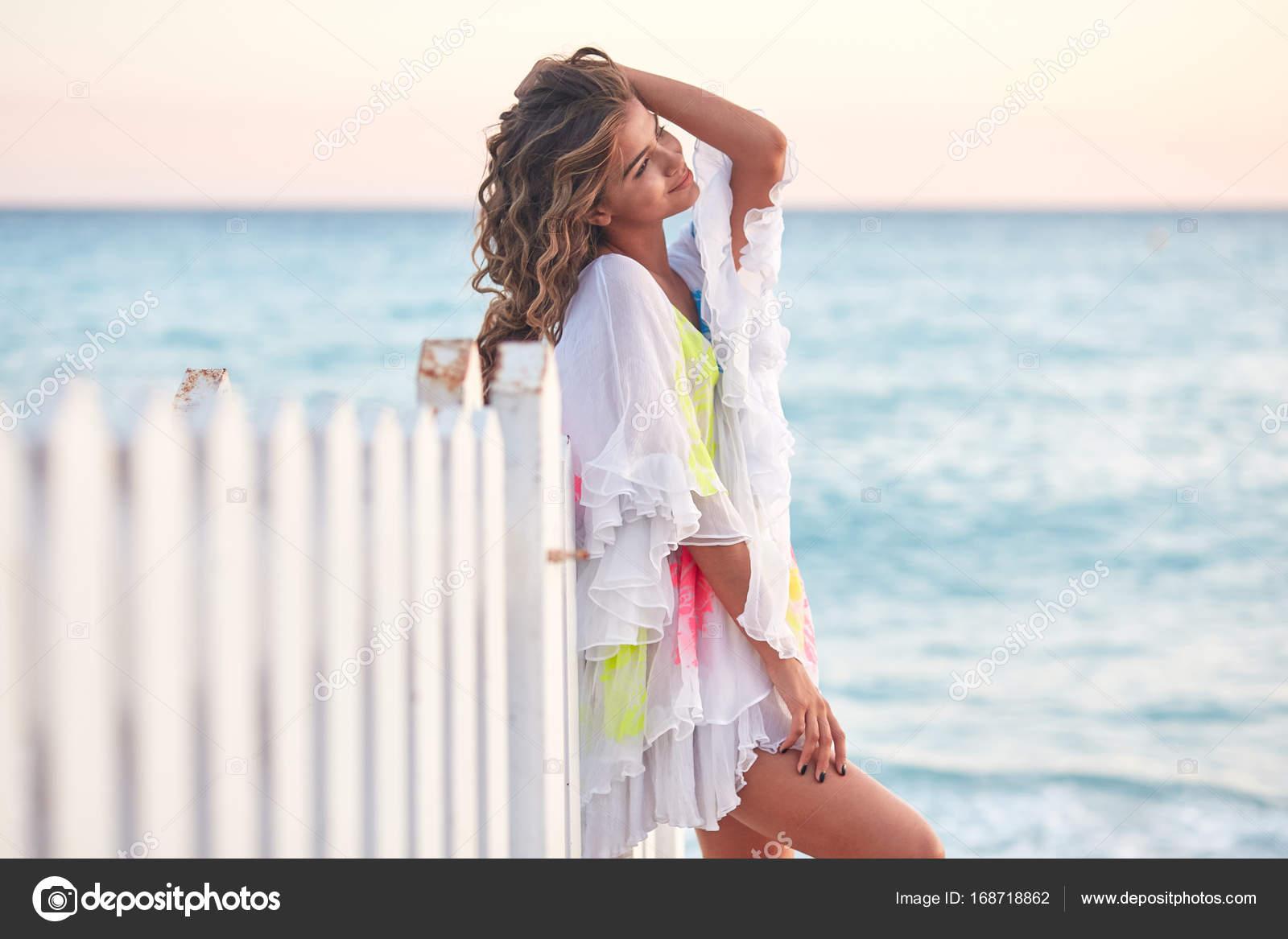 Szép szexi mosolygó fiatal nő modell jelentő közelében a tenger partján  lenyűgöző nyári strand ruha viselése 9ca6c4a99f