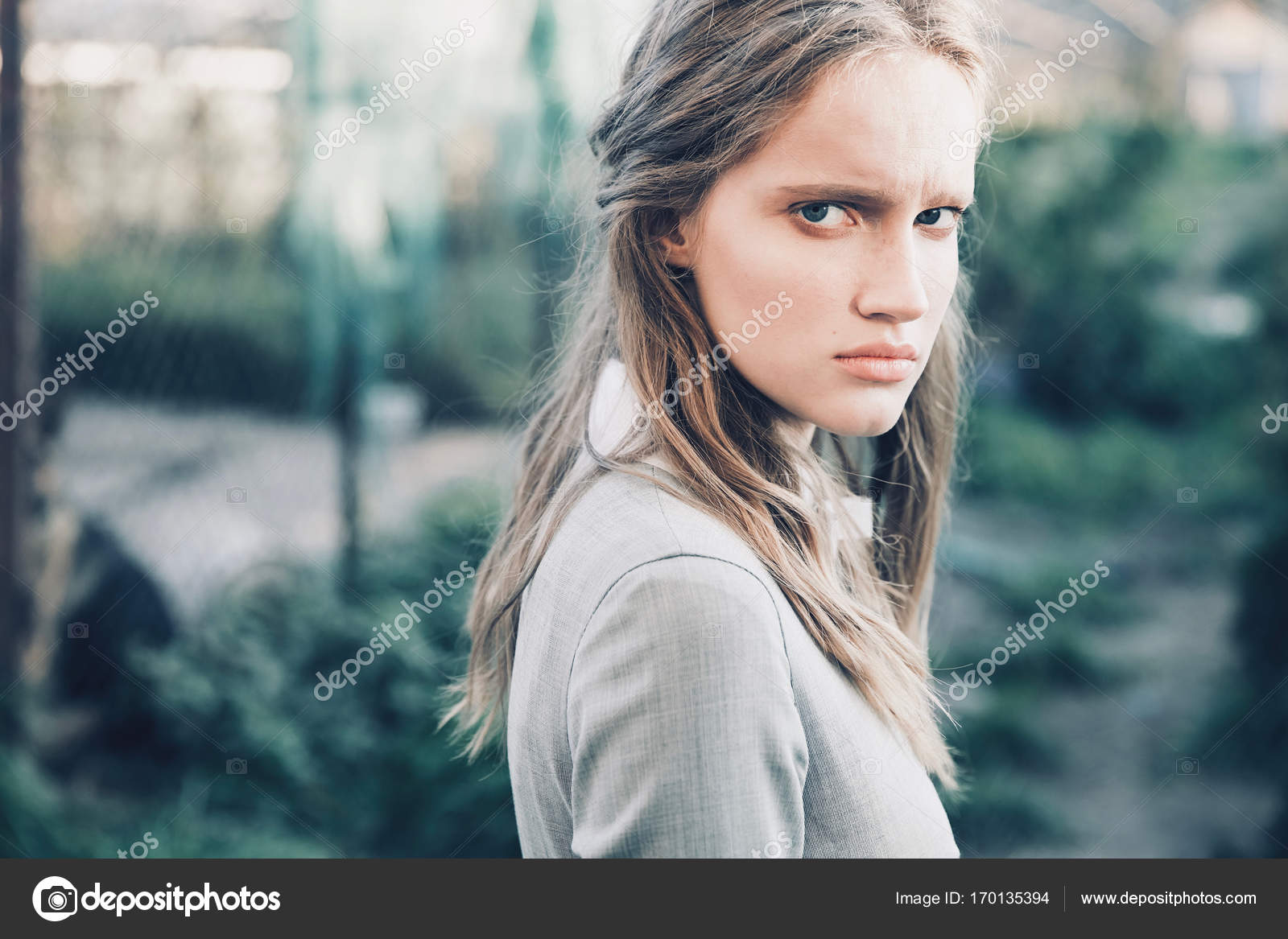 6c17c26115235 Portrait of young beautiful serious girl with long brown hair wearing light  gray dress in retro
