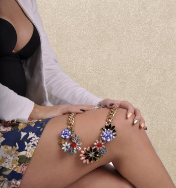 beautiful girl holding a necklace on her leg