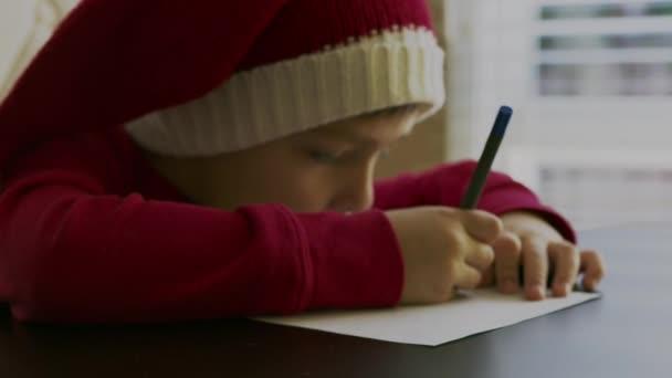 malý chlapec v červeném svetru a červeném santa klobouku s bílou bambulí sedící u stolu, držící pero v rukou a píšící nebo kreslící na prázdný bílý kus papíru před jasným