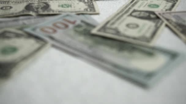 Amerikanische Dollars liegen auf einem glänzenden Hintergrund. Die Kamera bewegt sich langsam vorwärts und konzentriert sich auf Banknoten verschiedener Stückelungen. Geld in Zeitlupe