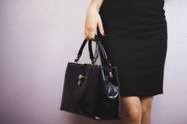 Fashionable woman holding trendy bag.