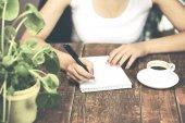 woman  writing in an agenda