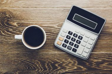 calculator and coffee on  table