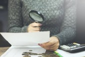 Businesswoman looking through a magnifying glass to documents note