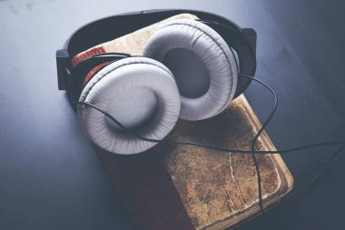 book cover and headphones over dark table