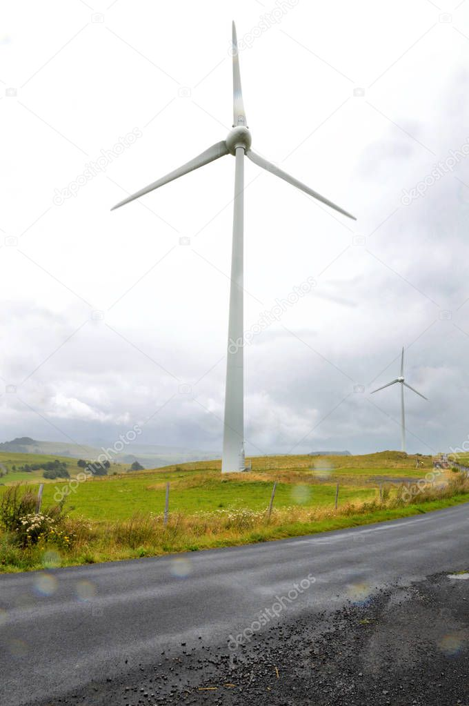 A wind turbine during a storm with wind and rain, in a mountainous region, at the top of a hill. It is a source of ecological electricity, which produces renewable energy.