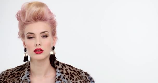 Krásná žena v kožichu s kreativními barvenými vlasy se dívá do kamery. Portrét blondýny se stylovým účesem. Módní koncept. Výrazná dívka s červenými rty a večerním make-upem.