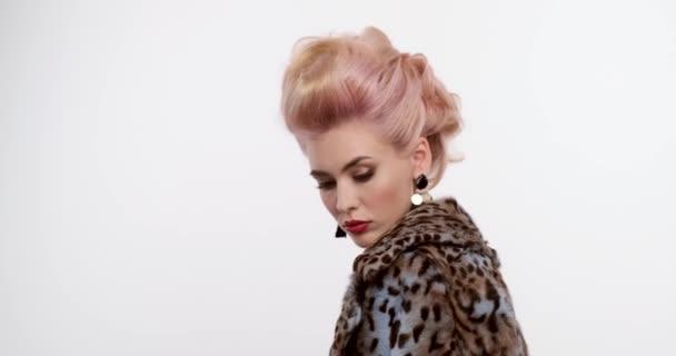 Gyönyörű nő, színes hajjal. Egy elegáns frizurájú szőke portré. Divatos elképzelés. Szoros arc egy szexi fehér lányról. Kifejező lány vörös ajkakkal és esti sminkkel. Lassú mozgás.