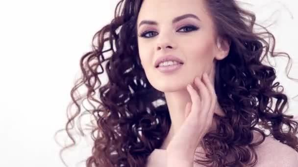 Schöne lächelnde Frau mit langen lockigen Haaren. Schönheit Gesicht. Modemodell. Modeschminke. Attraktive sexy Mädchen mit einem Smokey Eye Make-up. Großaufnahme Gesicht einer Frau. Zeitlupe 4k Filmmaterial.