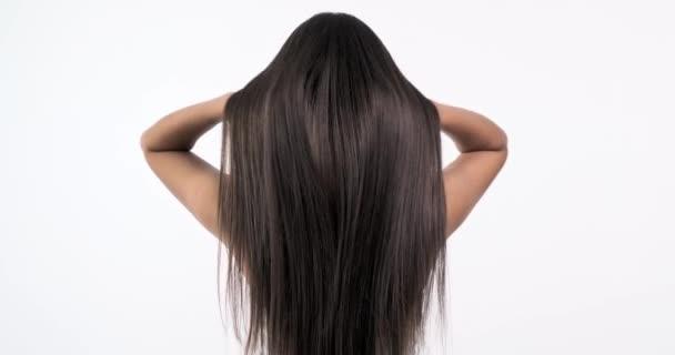 Frau bewegt lange Haare. Rückansicht. Mädchen schüttelt lange glatte Haare. Zeitlupenaufnahmen. Rückansicht. 4k. Weibliches Model flattert die Haare.