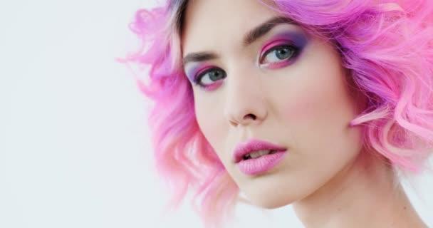 Stylová žena s módním účesem. Detailní portrét módního modelu s jasně fialovými vlasy. Krásná tvář s růžovým make-upem. Módní holka. Zpomalený pohyb.