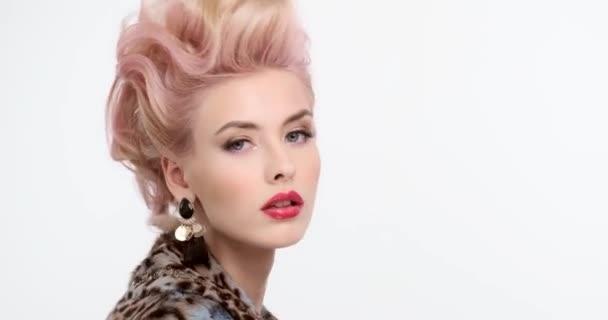 Moderní moderní žena v kožichu s kreativními barvenými vlasy se otočí a podívá se do kamery. Blondýna se stylovým účesem. Působivá dívka s červenými rty a večerním make-upem. Reálný čas