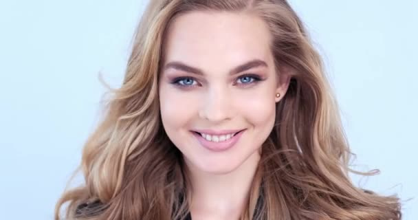 4K footage of a happy young blonde woman with curly long hair. Cheerful fashion model looks to the camera. Closeup smiling face of a caucasian girl. Joyful model posing at studio. Slow motion.