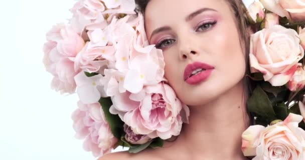 Face with flowers. Beautiful caucasian woman with fresh skin. Closeup female face with flowers. Beauty concept. Skin care. Young girl with natural makeup. 4k. Slow motion