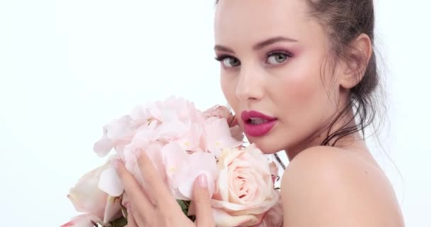 Tvář s květinami. Krásná běloška s čerstvou pletí. Detailní ženský obličej s květinami. Krásný koncept. Péče o pleť. Mladá dívka s přirozeným make-upem. Žena se otočí ke kameře. 4k. Zpomalený pohyb