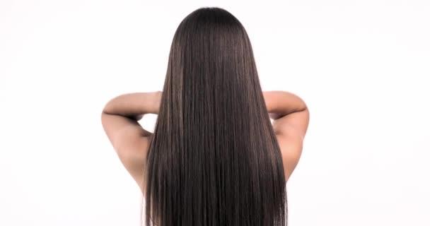 Žena hýbe dlouhými vlasy. Zadní pohled. Dívka třese dlouhými rovnými vlasy. Zpomalené záběry. Zadní pohled. 4k. Žena model je chvějící se vlasy.