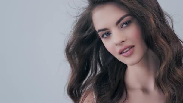 schöne Frau mit langen lockigen braunen Haaren. Model blickt im Studio in die Kamera. Nahaufnahme Gesicht einer attraktiven brünetten Frau. sexy Modell mit einem sexy Look. 4k Filmmaterial. Zeitlupe.