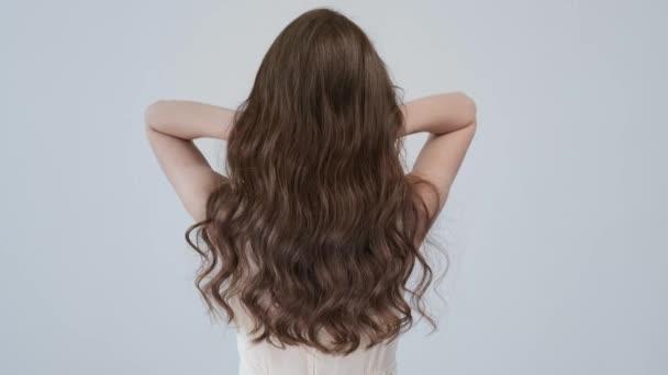 Frau bewegt lange Haare. Rückansicht. Mädchen schüttelt lange glatte Haare. Das weibliche Model hat flatternde Haare. Zeitlupenaufnahmen. Rückansicht