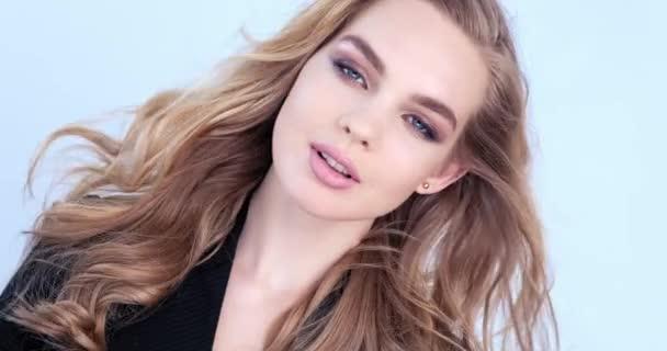 schöne junge blonde Frau mit langen Haaren. Modelmodel blickt in die Kamera. Nahaufnahme atemberaubende Gesicht eines kaukasischen Mädchens. sexy Model mit schönen blauen Augen. Zeitlupe. Schönheitskonzept.