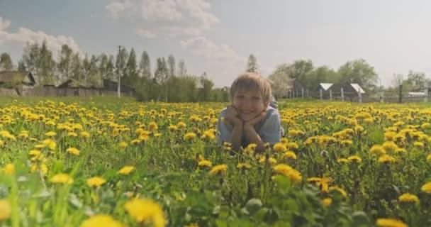 Csinos kaukázusi fiú fekszik a tavaszi réten, és úgy néz ki. Boldog gyermek fekszik a százszorszépek mezején, közelről. Aranyos mosolygós arca van egy szőke fiúnak, a réten. Boldogság és gyermekkor. Lassú mozgás.