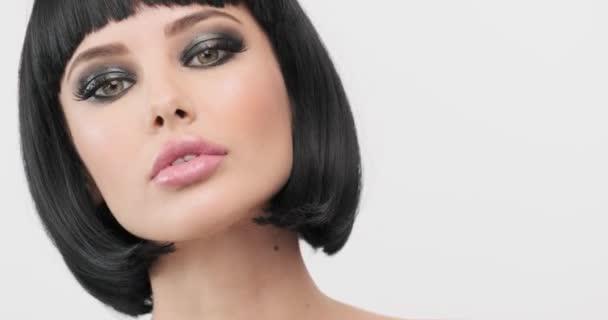 Porträt eines Models mit Smokey Eyes Make-up. junge Frau flirtet. Nahaufnahme Gesicht eines sexy weißen Mädchens. schöne Brünette mit einer Bob-Frisur. ausdrucksstarkes Mädchen mit langen Wimpern. 60 fps.