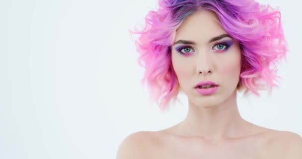 Closeup portrait of a fashion model with bright purple hair.  Stylish woman with fashion hairstyle. Beauty face with a pink makeup. Fashionable girl.  Art concept. 4k footage. Real time.