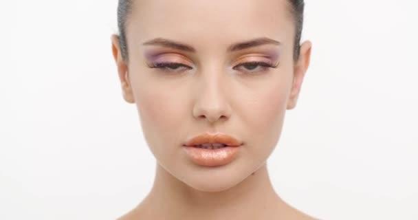 Detailní tvář mladé ženy s čistou pletí obličeje. Péče o pleť. Krásná dívka se sexy vzhled otočí na kameru. Krásná zdravá žena s čerstvou pletí obličeje přes bílé pozadí. Zpomalený pohyb