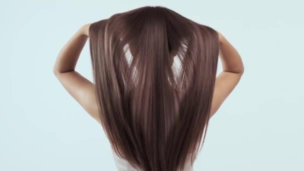 Frau bewegt lange Haare. Rückansicht. Mädchen schüttelt lange glatte Haare. Das weibliche Model hat flatternde Haare. Zeitlupenaufnahmen. Rückansicht. Ingwer. Rothaarige.