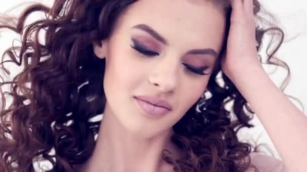 Beautiful smiling woman with long curly hair.  Beauty face. Fashion model. Fashion makeup. Attractive sexy  girl with a smokey eye makeup.  Closeup face of a woman. Slow motion 4k footage.