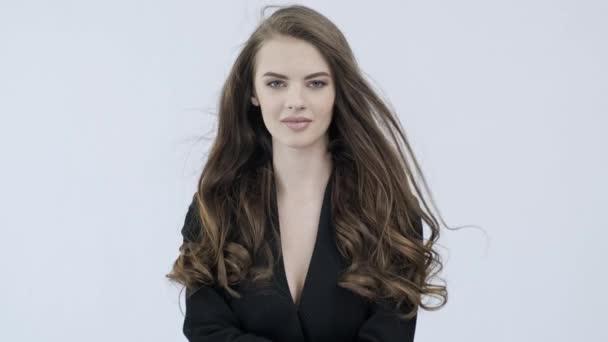 4k Filmmaterial einer schönen jungen Frau mit lockigen langen braunen Haaren. Modelmodel blickt in die Kamera. atemberaubendes Gesicht eines kaukasischen Mädchens. sexy Modell mit schönen Augen. Zeitlupe. Schönheitskonzept