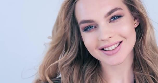4k Filmmaterial einer glücklichen jungen blonden Frau mit lockigen langen Haaren. Fröhliches Mode-Model blickt in die Kamera. Nahaufnahme lächelndes Gesicht eines kaukasischen Mädchens. freudiges Model posiert im Studio. Zeitlupe.