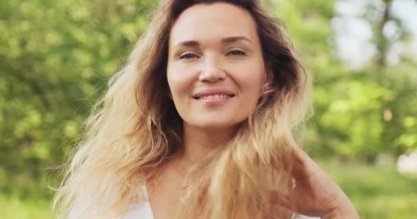 Közelkép egy boldog felnőtt nő arcáról a természetben, aki a kamerába néz. Vidám felnőtt lány a parkban. Szabadtéri portré egy szőke nőről, hosszú göndör hajjal a parkban. Lassú mozgás..