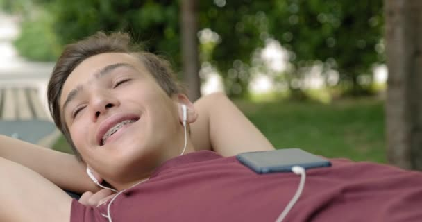 Portrait of happy teenage boy in earphones lying on a bench in a park and relaxing.  Teenager listen to the music in earphones. Smiling young handsome man listens to music in a headphone, outdoors.