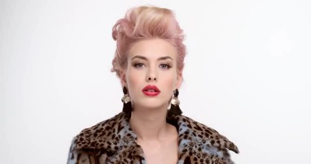 Gyönyörű nő foltos bundában, színes hajjal, fehér háttér felett pózol. Egy elegáns frizurájú szőke portré. Expresszív lány piros ajkak, esti smink és nagy fülbevalók.