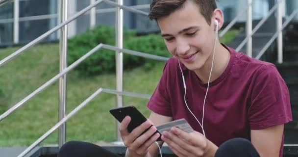 Teen makes online purchases using a credit card and mobile phone.  Smiling young man makes online shopping using cell phone with bank card, outdoors. Boy uses smartphone and credit card. Real time.